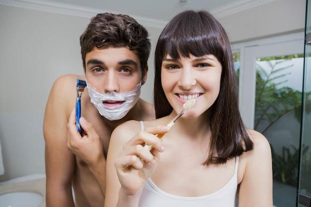 Rotina do banheiro para o jovem casal feliz, escovar os dentes e fazer a barba no espelho