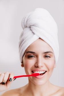 Rotina matinal. garota depois do banho, escovando os dentes na parede branca.