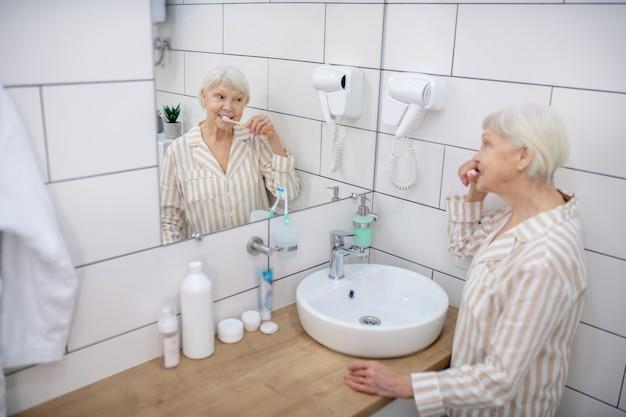 Rotina matinal. mulher idosa escovando os dentes no banheiro