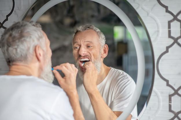 Rotina matinal. um homem escovando cuidadosamente os dentes pela manhã