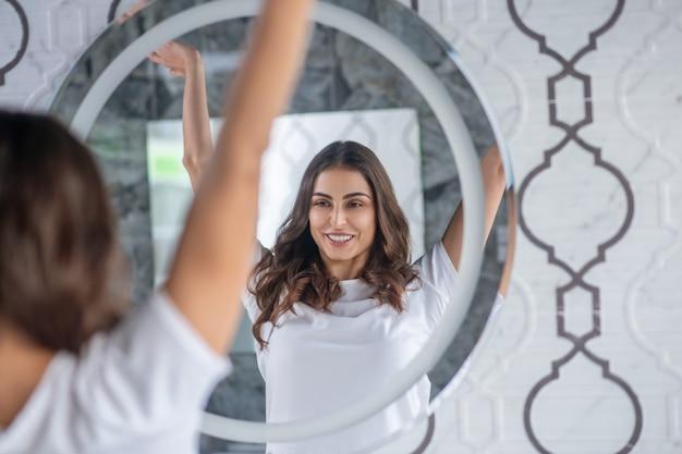 Rotina matinal. uma mulher esticando as mãos perto do espelho