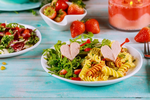 Rotini colorido, corações do conceito do dia dos namorados da salada dos cachorros quentes e dos vegetais.