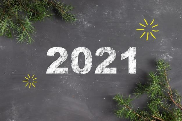 Rotulando 2021 em giz em um quadro cinza com galhos de pinheiro