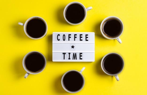 Rotulando a hora do café em um fundo amarelo com canecas de café expresso