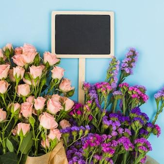 Rótulo de lousa em branco dentro do buquê de flores contra o fundo azul