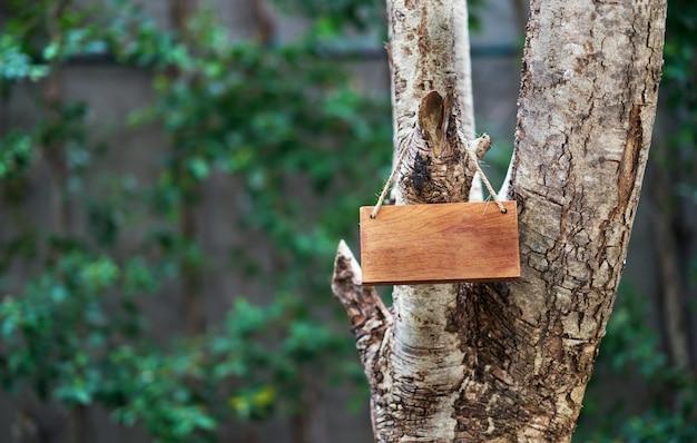 Rótulo de madeira pendurar na árvore no fundo da natureza para o conceito de cuidados de terra