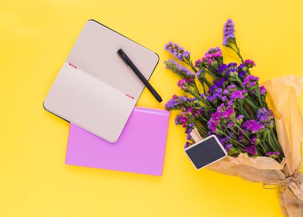 Rótulo de quadro-negro; flores roxas; diário e caneta no pano de fundo amarelo