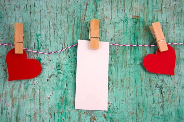 Rótulo em branco branco com lugar para texto e papel corações vermelhos pendurado em prendedores de roupa em uma corda