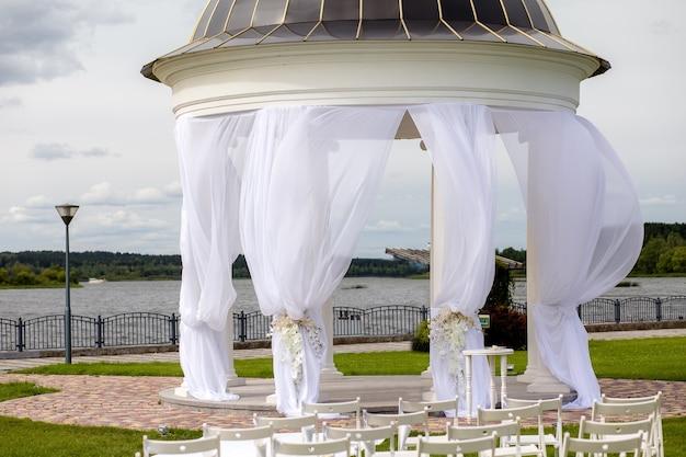 Rotunda, coluna, estilo palácio. arco para casamentos e cerimônias de despedida decorado com tule branco. design e arquitetura, casamentos. decoração de casamento Foto Premium