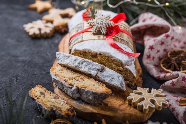Roubado. sobremesa de natal caseira fatiada stollen com frutas secas e castanhas na mesa rústica de pedra com canela, fatias de laranja, galhos de árvores de natal, pão de gengibre, foco seletivo