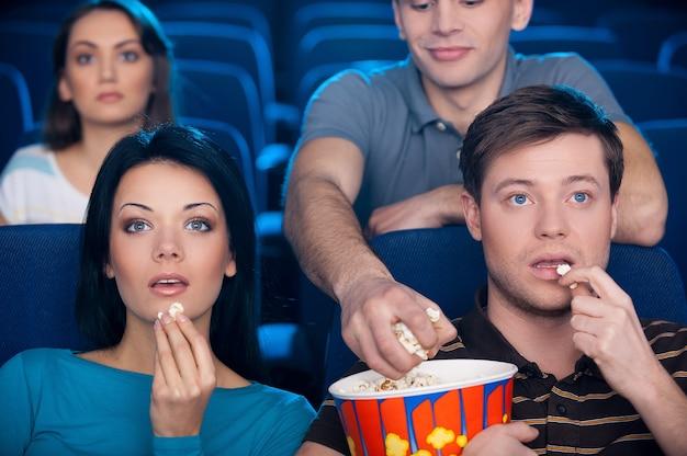 Roubando pipoca. jovem casal animado comendo pipoca e assistindo filme no cinema enquanto um homem do banco de trás roubando sua pipoca
