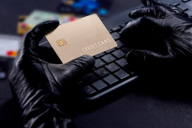 Roubo de internet - mãos enluvadas de ladrão com cartão de crédito atrás do laptop