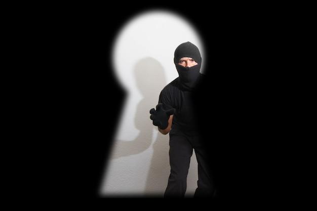 Roubo de uma casa. atenção. o ladrão se esgueira por uma fechadura para poder abrir a porta