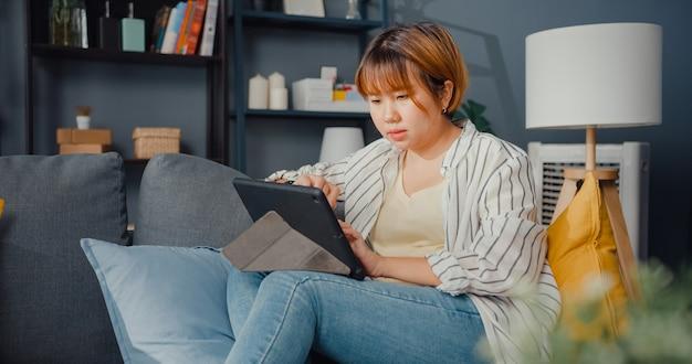 Roupa casual para senhora asiática freelance usando aprendizado on-line com tablet na sala de estar de casa