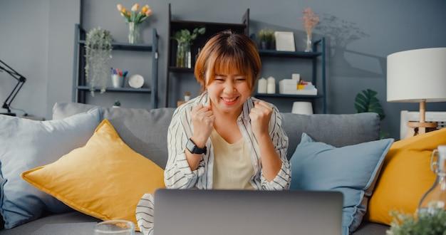 Roupa casual para senhora asiática freelance usando laptop, aprendendo on-line na sala de estar de casa