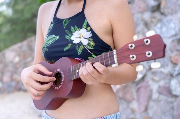 Roupa de banho asiático novo do desgaste de mulher que joga no ukulele na praia. conceito de temporada de verão.