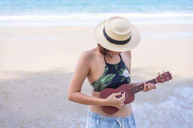 Roupa de banho asiático novo do desgaste de mulher que joga no ukulele na praia. temporada de verão