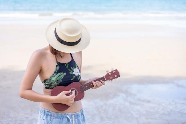 Roupa de banho asiático novo do desgaste de mulher que joga no ukulele na praia.