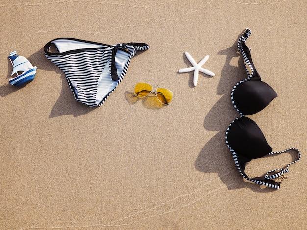Roupa de banho e óculos de sol na areia na praia do por do sol.