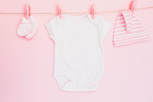 Roupa de bebê pendurada em rosa