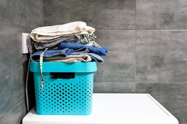 Roupa de cama dobrada, jeans, toalhas em uma caixa azul contra o fundo de azulejos de concreto cinza no banheiro. pilha de roupas sujas e roupas no canto em uma máquina de lavar