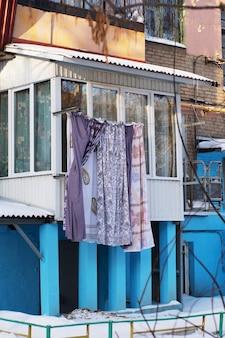 Roupa de cama multicolorida pendurada em uma varanda ou varal em uma casa rural azul feita de madeira e pedra.