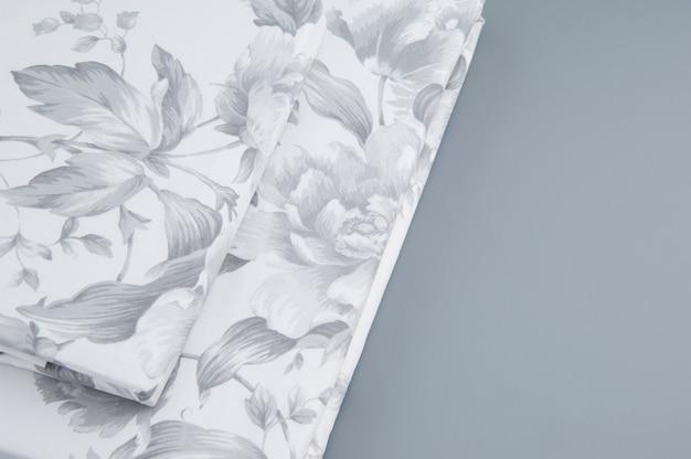 Roupa de cama nova dobrada com padrões em fundo cinza, vista de cima