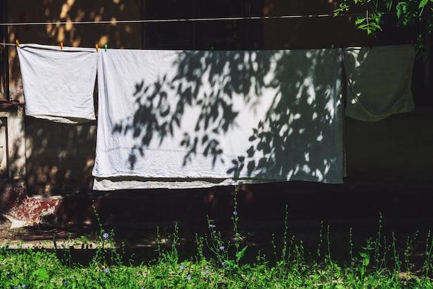 Roupa de cama que pendura na corda com os pregadores de roupa no dia ensolarado.