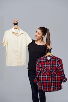 Roupa de colheita de mulher, segurando duas camisas escolhendo