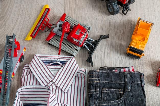Roupa de menino perto de conjunto de brinquedo do carro. camisa listrada, calça jeans perto de carros amarelos e vermelhos.