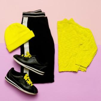 Roupa de moda para mulheres. roupas pretas elegantes e acessórios brilhantes. esportes urbanos. mínimo. vista de cima tênis calça gorro