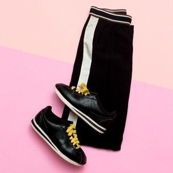 Roupa de moda para mulheres. roupas pretas elegantes. sports urban. mínimo. vista superior de tênis e calças