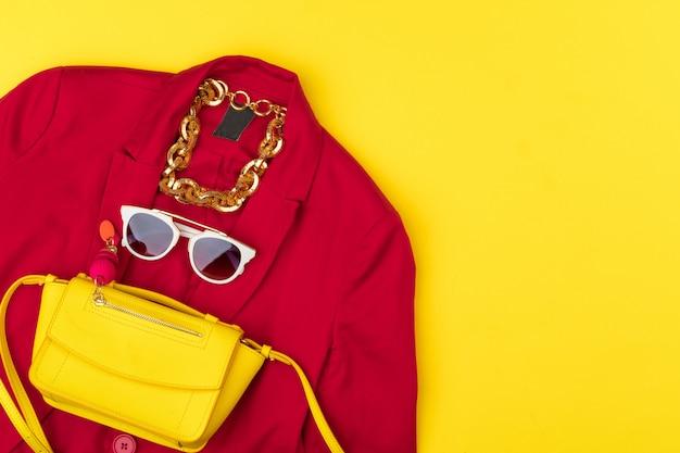 Roupa de mulher na moda com acessórios em fundo amarelo brilhante
