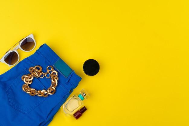 Roupa de mulher na moda com acessórios na mesa amarela brilhante