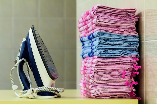 Roupa de passar roupa com gerador de vapor. uma pilha de toalhas passadas ao lado do ferro. placa de teflon única coberta com pequenos orifícios.