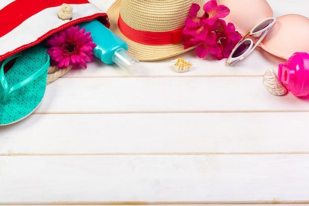 Roupa de praia e acessórios em um fundo branco de madeira