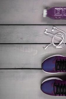 Roupa de treino de mulher de visão aérea. tênis de corrida roxos, garrafa de água