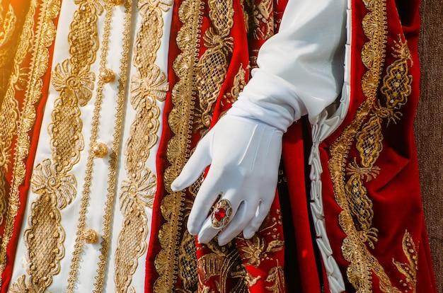 Roupa de uma histórica mulher imperial com elementos vermelhos, uma mão em luvas brancas e um anel com uma pedra preciosa.