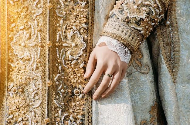 Roupa de uma histórica mulher imperial com tons pastel, uma mão com um anel com uma pedra preciosa.