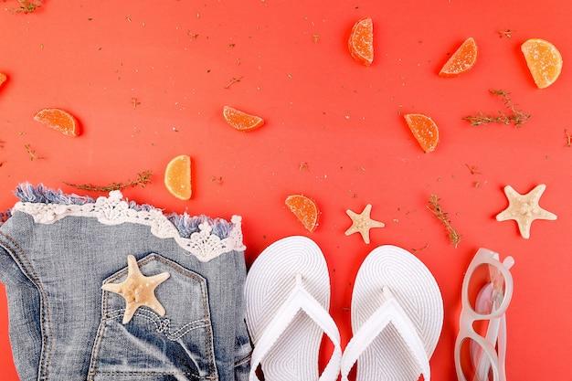 Roupa de verão das mulheres. shorts jeans e chinelo branco e óculos de sol em fundo laranja. postura plana. copie o espaço.