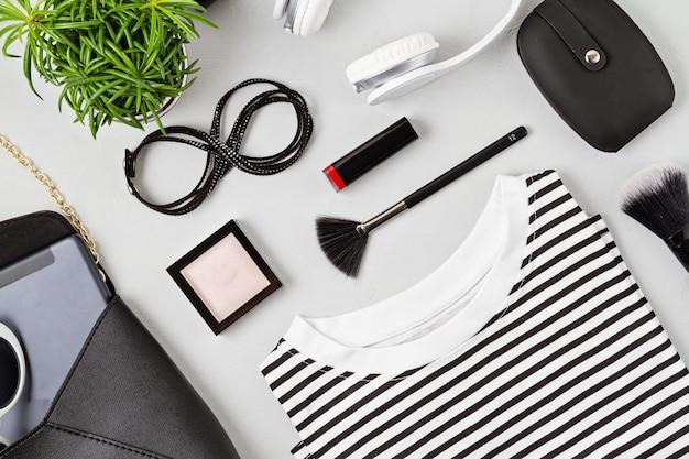 Roupa e acessórios de moda mulher, bolsa, bloco de notas, maquiagem e fones de ouvido nas cores preto e branco. beleza, roupa urbana e conceito de tendências da moda. camada plana, vista superior