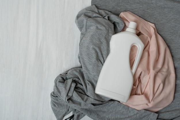 Roupa e garrafa com detergente. vista do topo