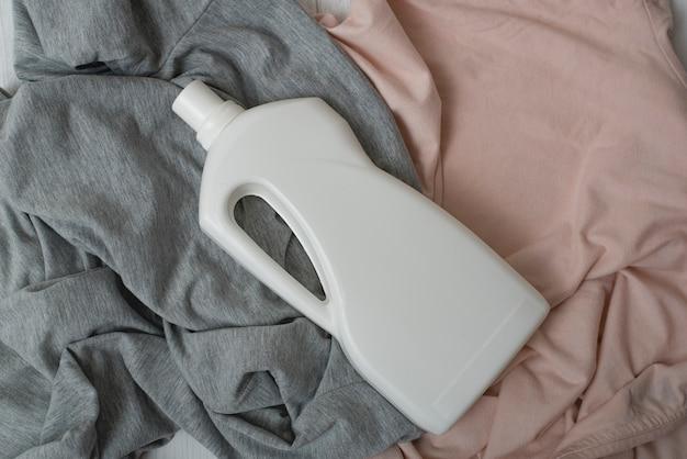 Roupa e garrafa com detergente.