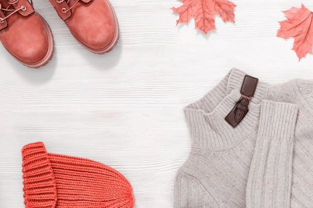 Roupa feminina, botas, blusa de malha e boné.