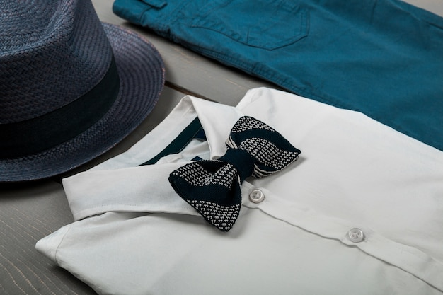Roupa masculina com fundo de madeira, roupas da moda infantil, fedora cinza, calça azul marinho, camisa branca, gravata borboleta preta, vista superior, postura plana, espaço de cópia.