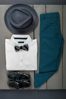 Roupa masculina com fundo de madeira, roupas de moda infantil, fedora cinza, calça azul marinho, camisa branca, gravata borboleta preta e sapatos de barco para menino, vista superior, postura plana, cópia espaço.