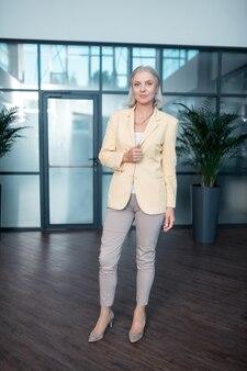 Roupa oficial. bonita empresária caucasiana de cabelos grisalhos em elegante traje oficial em pé dentro de casa enquanto olha para a frente dela