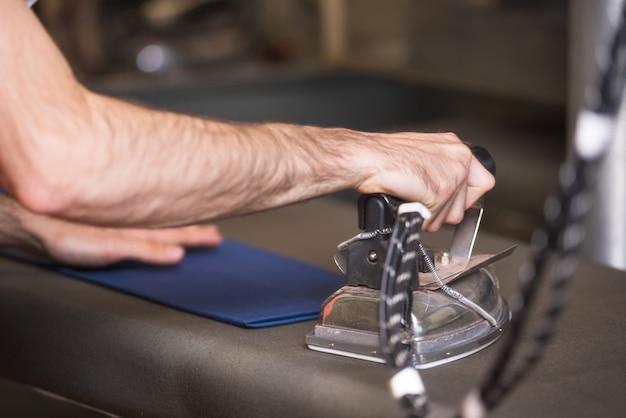 Roupa passando do alfaiate irreconhecível com ferro antiquado do metal no estúdio tradicional da oficina.