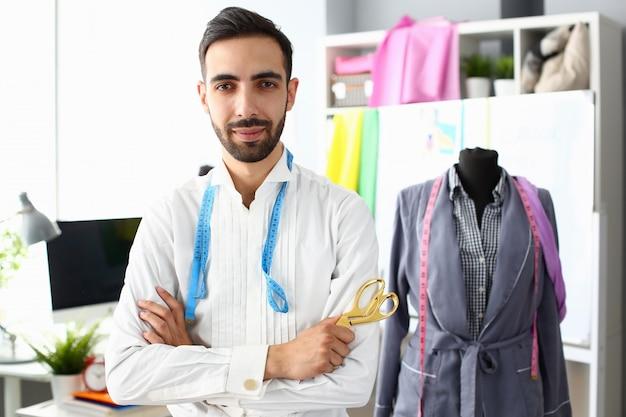 Roupa que cria o trabalho do desenhador de moda da profissão. esgoto elegante confiante em pé com uma tesoura