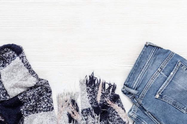 Roupa quente e confortável para clima frio. calças de ganga e cachecol bonito quente em madeira branca com espaço de cópia. vista do topo. postura plana.